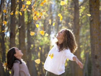 Madre e hija jugando con hojas de otoo